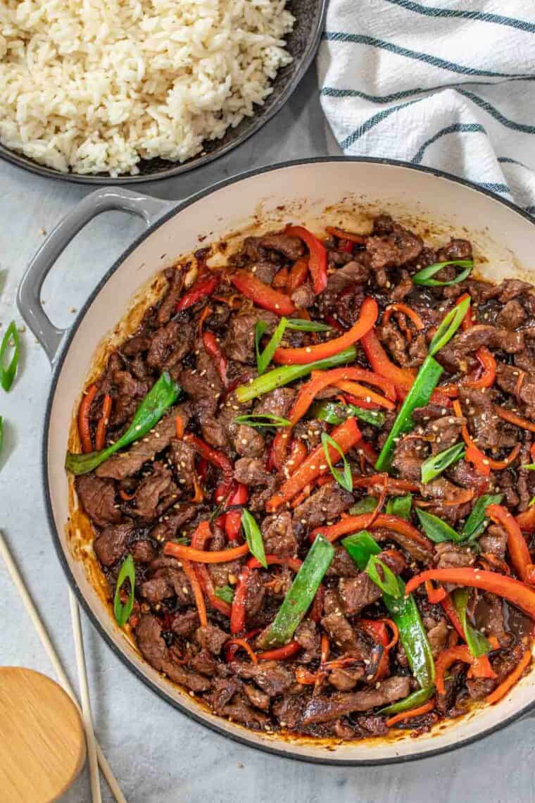 Mongolian beef in a skillet topped with sesame seeds and chopped green onion.