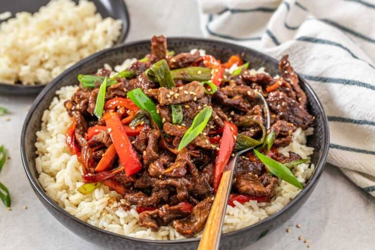 Mongolian beef in a black plate with rice and a metal spoon topped with fresh green onion.
