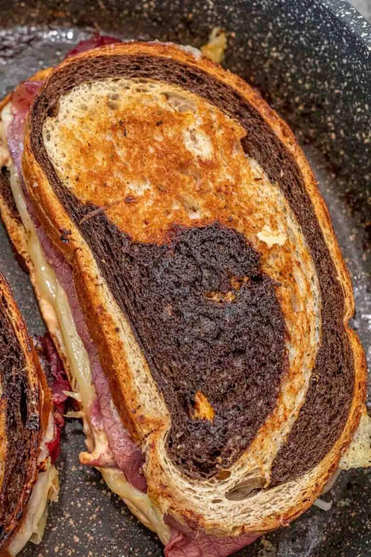 Rueben sandwich in a skillet with crispy rye bread.