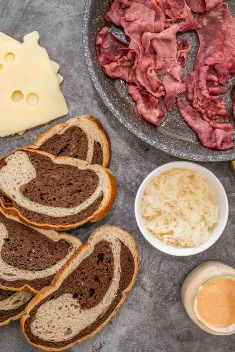 Corned beef, swiss cheese, rye bread, sauerkraut, and rye bread sliced laid out on cutting board.