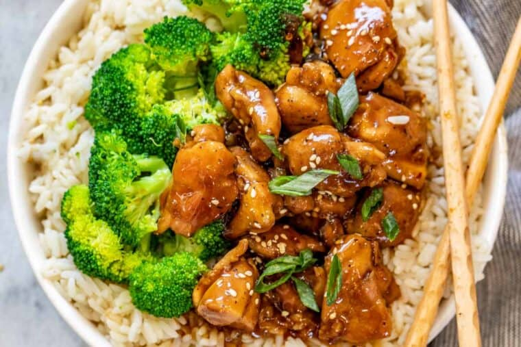 A white bowl of rice, broccoli, and chicken teriyaki topped with green onions and sesame seeds.