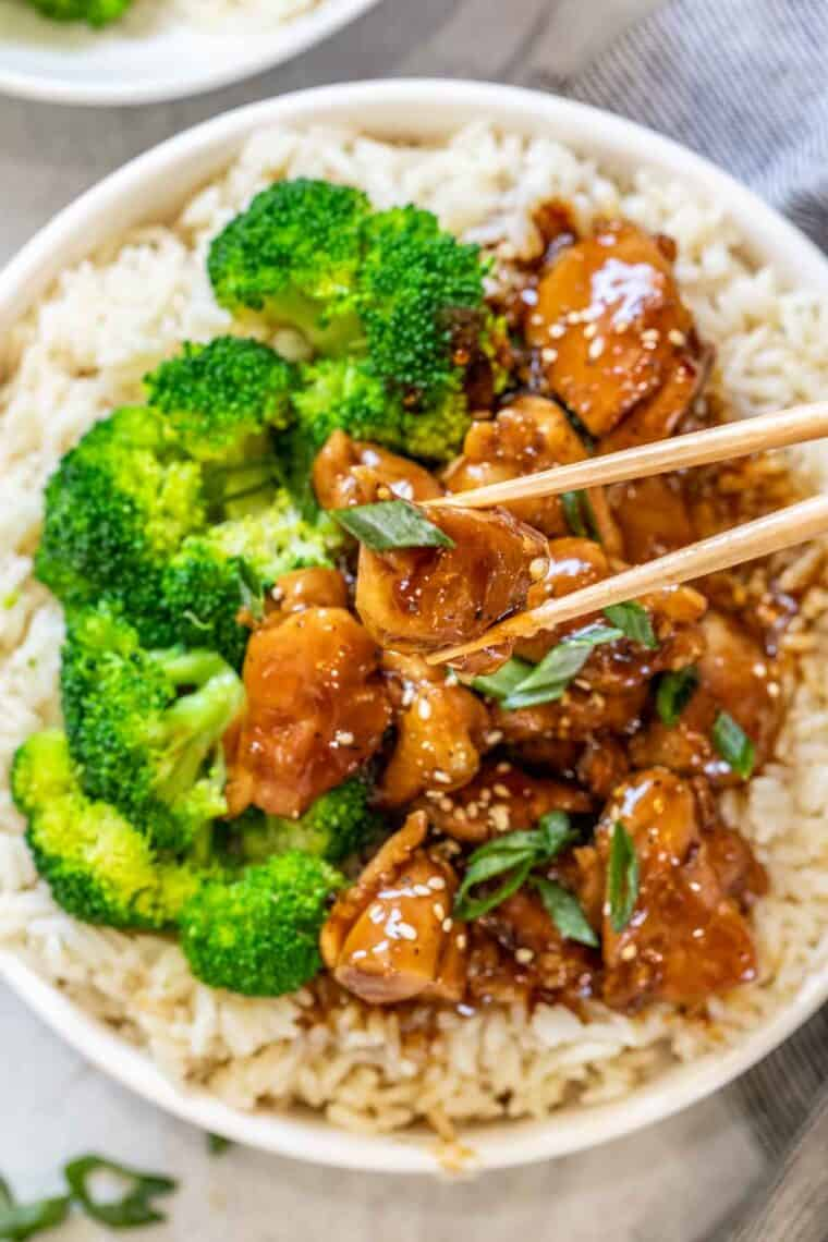 Chicken teriyaki bowls with a chop stick with a piece of chicken.