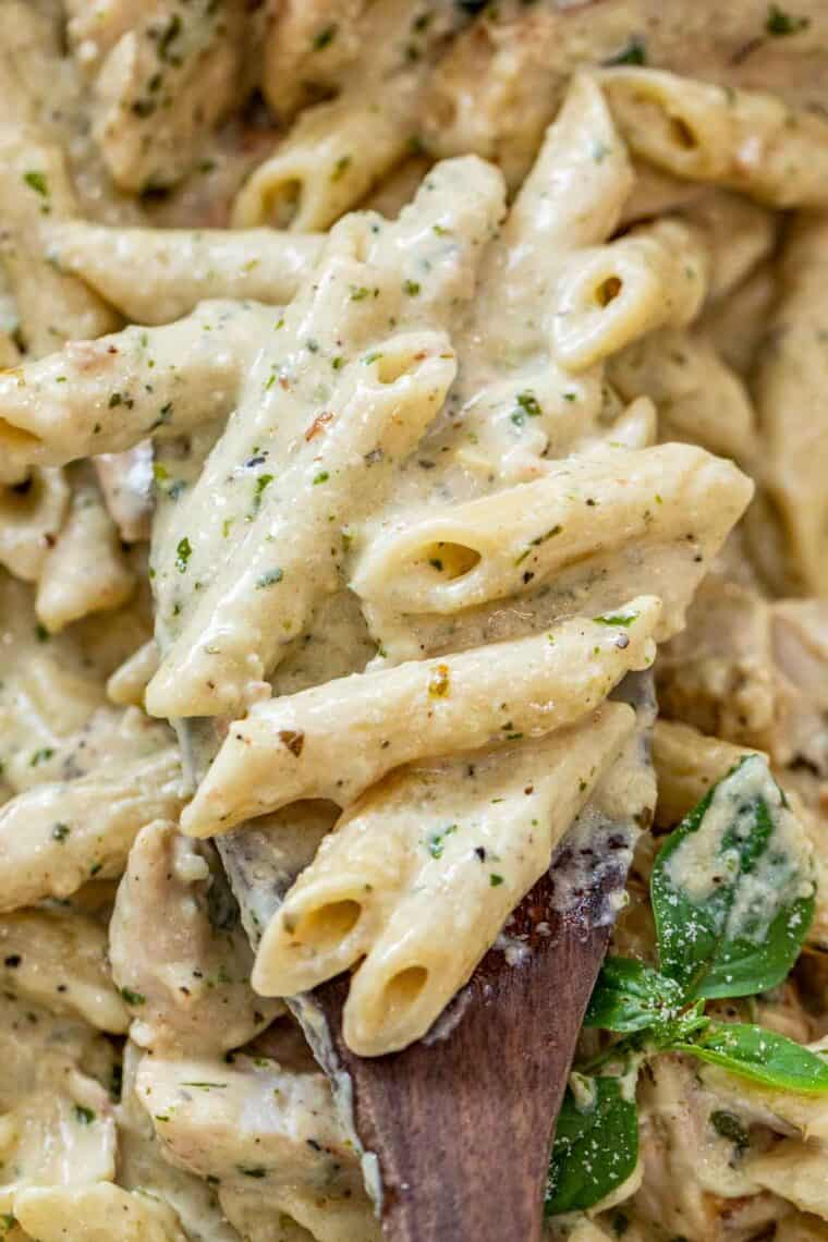 A spoonful of creamy pesto pasta topped with fresh basil.