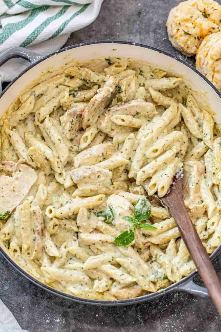 Pesto pasta in a gray deep skillet with a wooden spoon full of alfredo pasta.