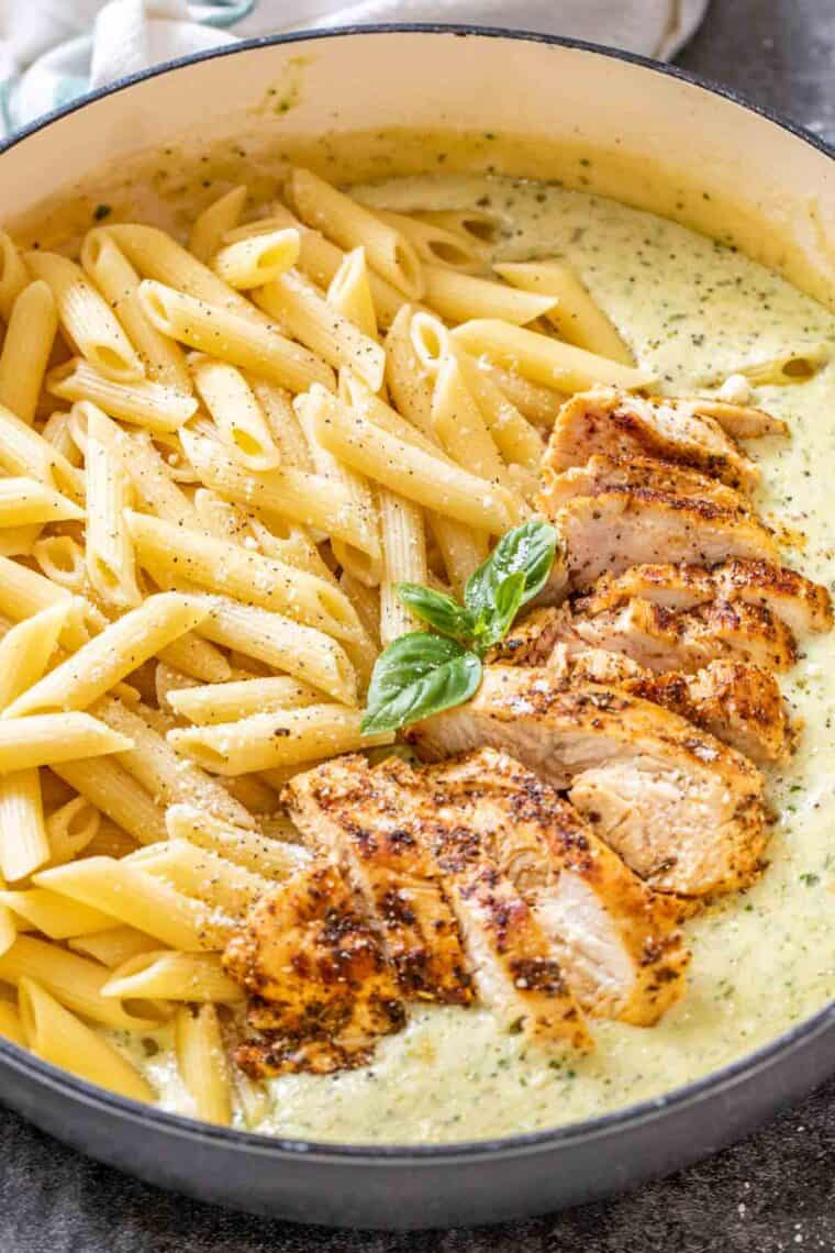 Pasta, chicken, and pesto alfredo sauce in a gravy skillet unmixed.