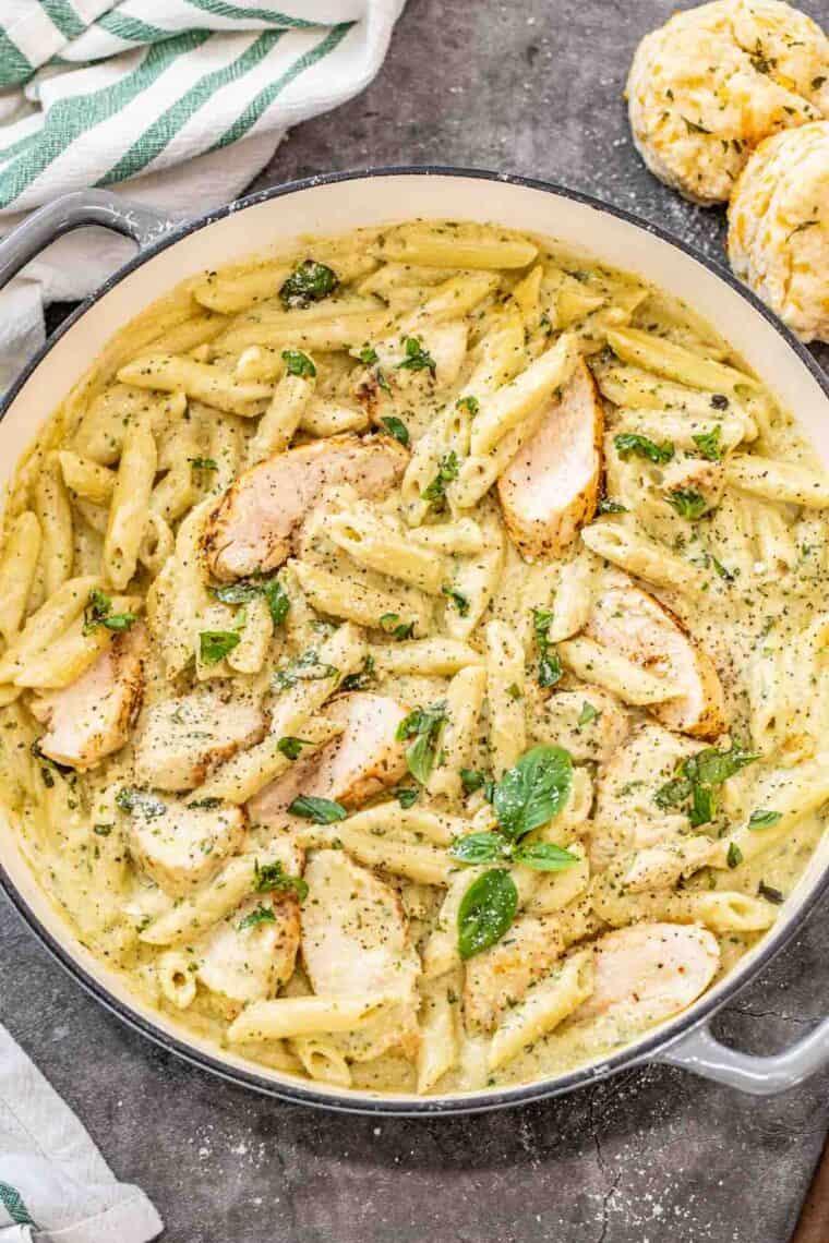 Creamy chicken pesto pasta in a pan with chopped basil pesto.