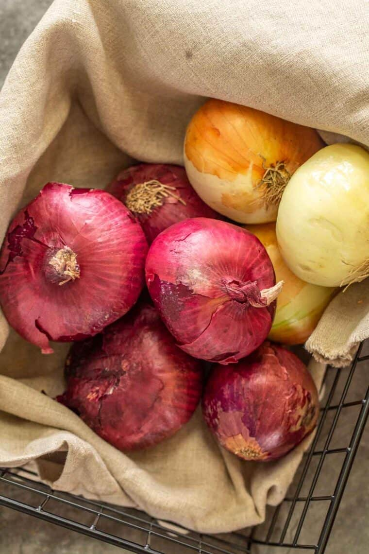 A basket of red onions, and sweet onions with a rag.