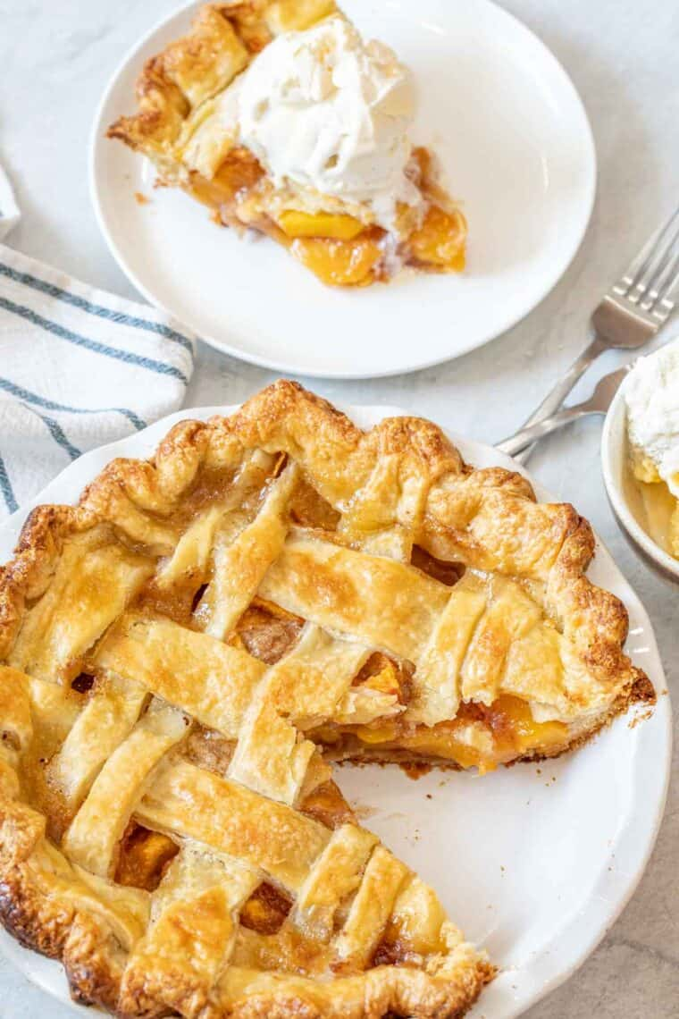 Peach pie in a pie dish next to a plate with a slice of pie topped with ice cream.