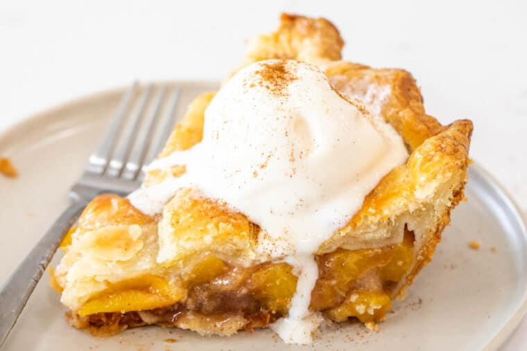 A slice of peach pie on a plate with a fork topped with a scoop of vanilla ice cream.