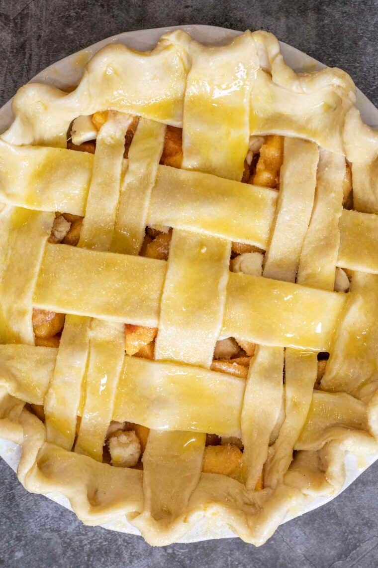 Peach pie made with a lattice topping brushed with egg wash and coarse sugar.