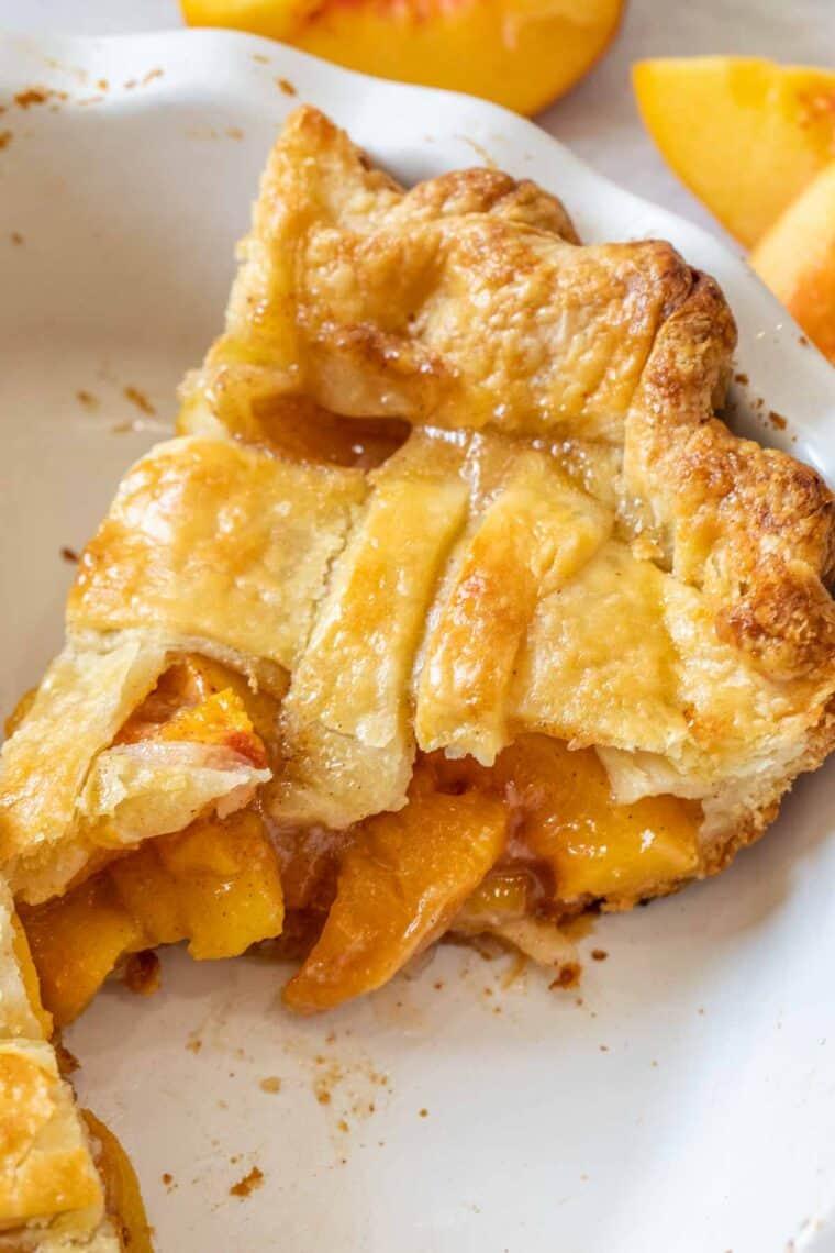 A slice of peach pie in a white casserole dish.
