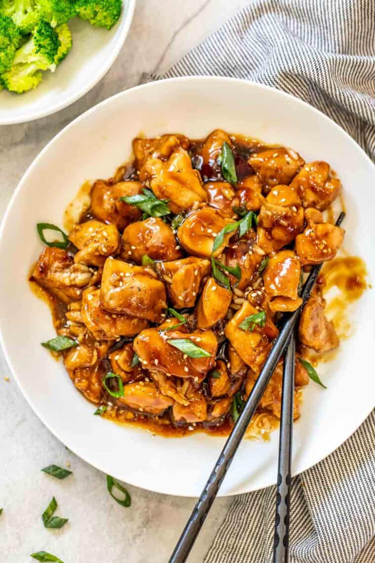 A bowl full of chicken in homemade teriyaki sauce topped with green onions and sesame seeds.