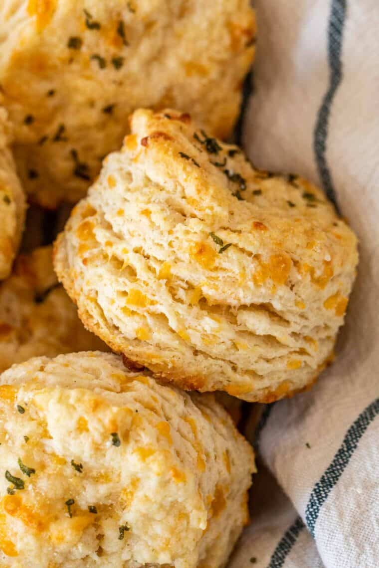 Cheddar biscuits topped with a garlic herb butter in a bread basket.