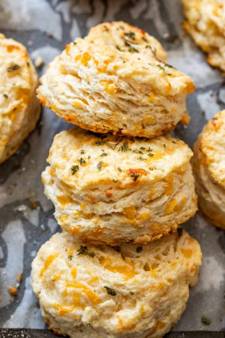Cheddar biscuits laid out on a baking sheet with three next to each other.