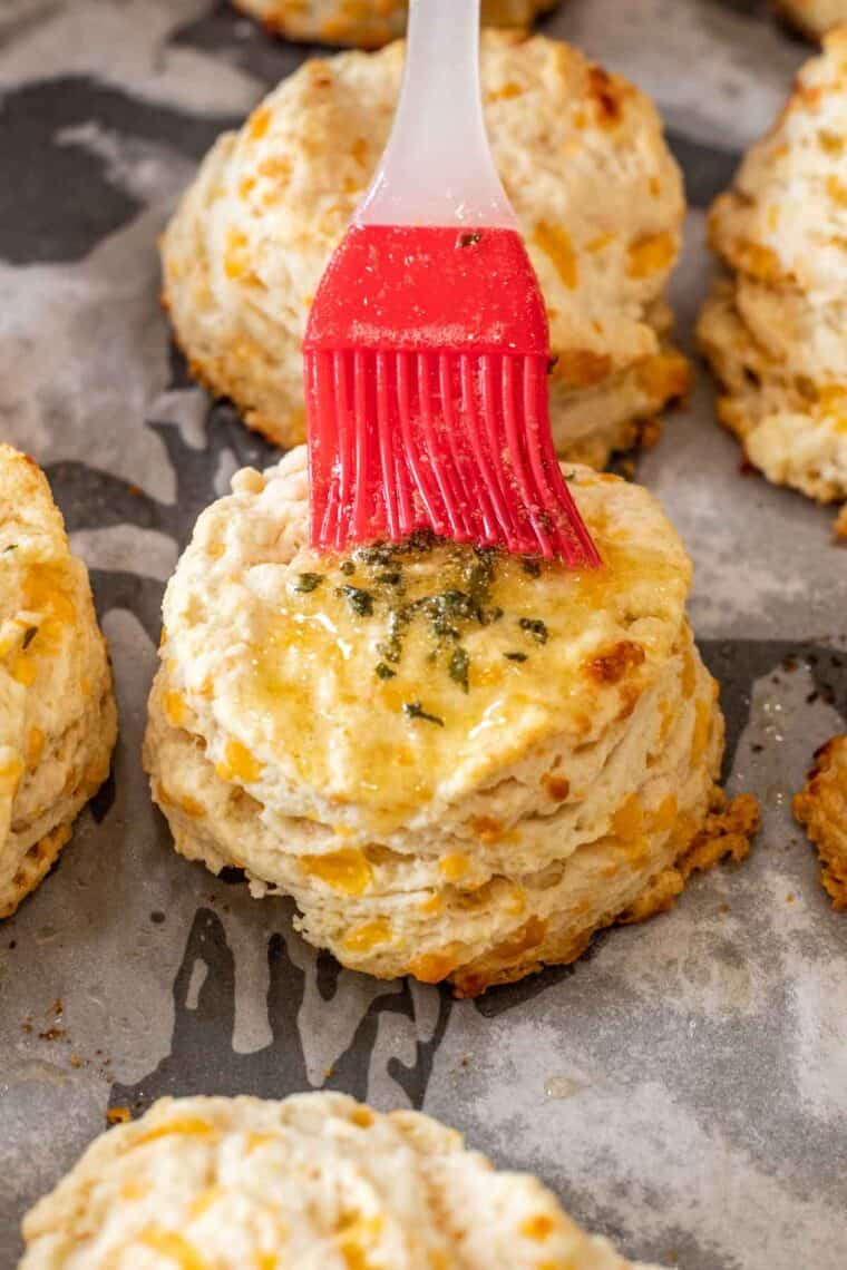 Cheddar biscuits on a baking sheet with a pastry brush of garlic butter.
